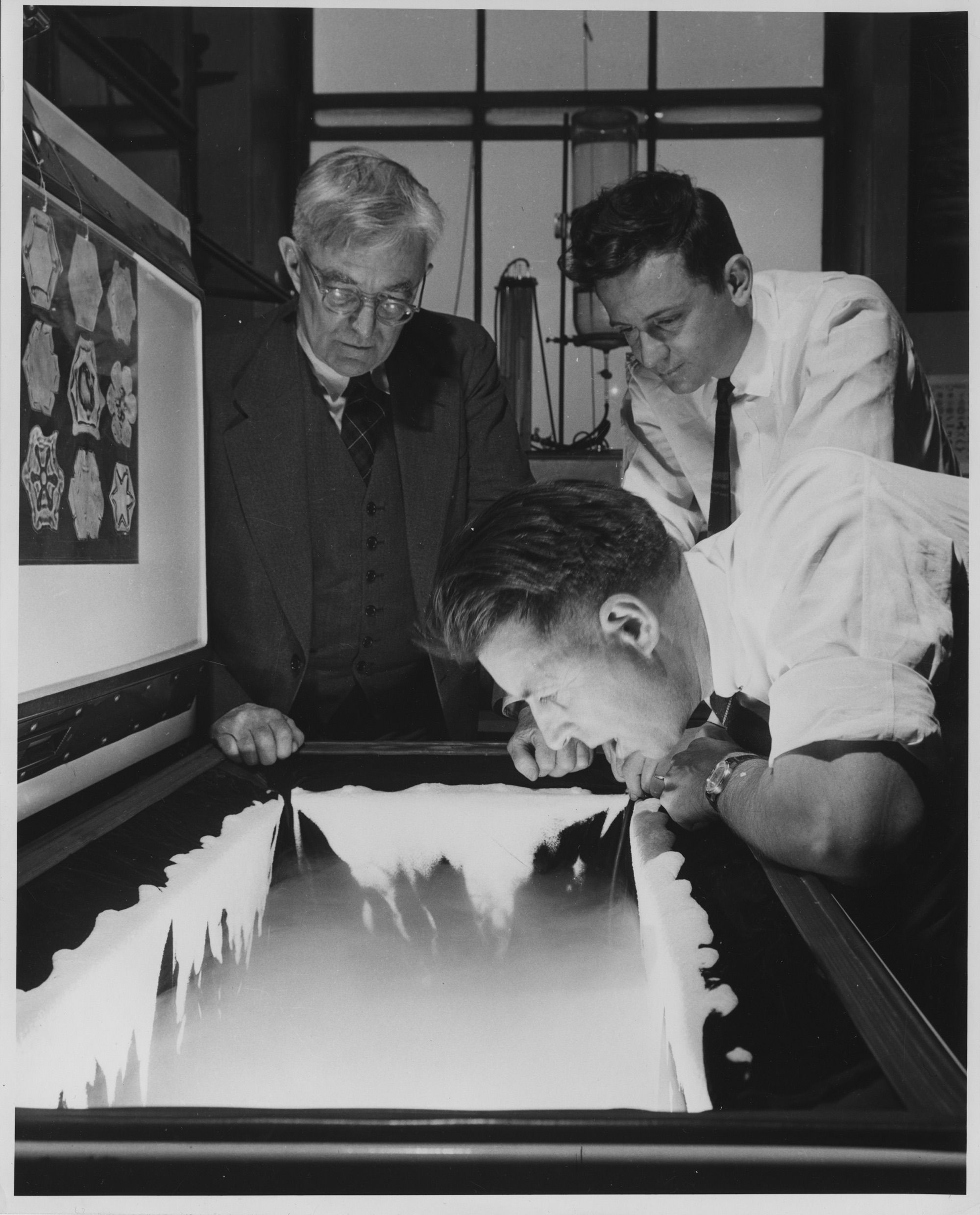 GE scientist Vincent Schaefer breathes a cloud into a freezer as colleagues Irving Langmuir and Bernard Vonnegut look on.